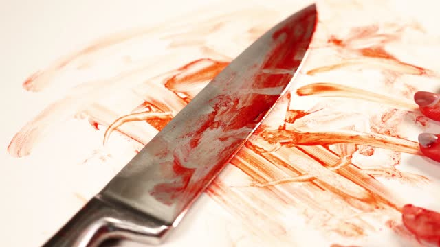 Person hand runs fingers on silver knife with blood closeup