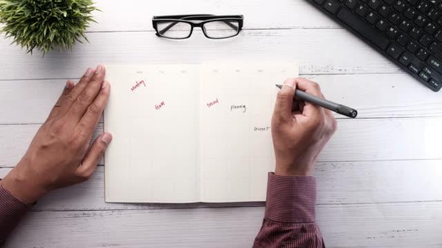 person hand skriva planer på anteckningsblock på skrivbordet - calendar workout bildbanksvideor och videomaterial från bakom kulisserna