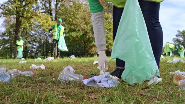 person holding a garbage bag and picking up rubbish in the local clean-up event - odzyskiwanie i przetwarzanie surowców wtórnych filmów i materiałów b-roll