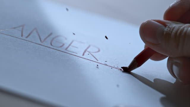 SLO MO LD Person holding a pencil and breaking the tip next to the inscription