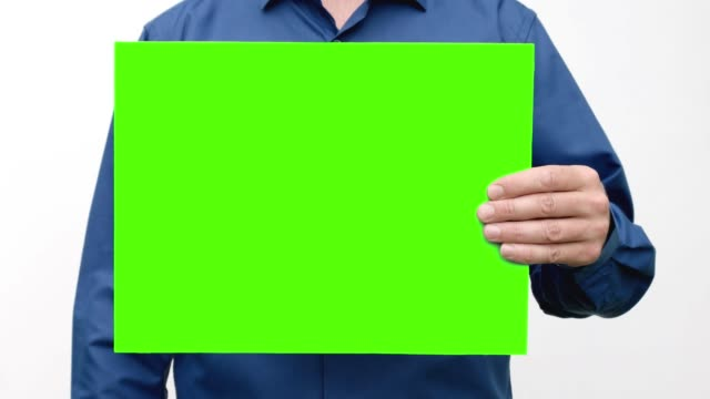 A person holds a green screen in front of him, raises it and lowers it