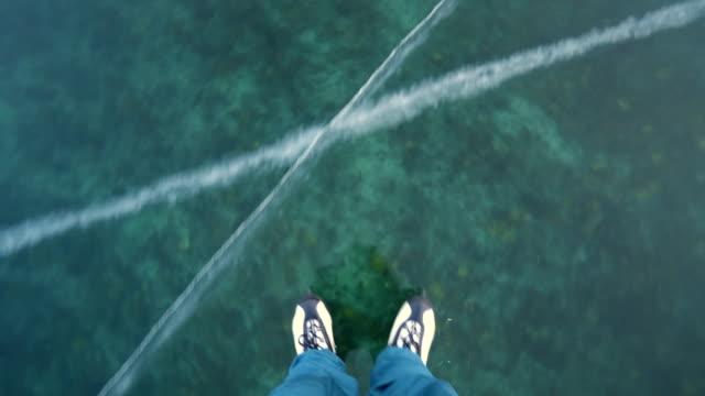 vídeos de stock e filmes b-roll de person ice skating on absolutely transparent ice of frozen lake baikal - lago baikal