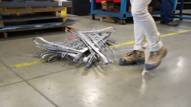 A person in a factory tripping over badly stored metal. An occupational health and safety topic.  Trips, Slips and falls account for the majority of safety incidents. A person in a factory tripping over badly stored metal. tripping falling stock videos & royalty-free footage