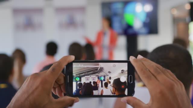 스마트폰으로 촬영하는 비즈니스 컨퍼런스에서 청중의 사람 - 영화 촬영 스톡 비디오 및 b-롤 화면