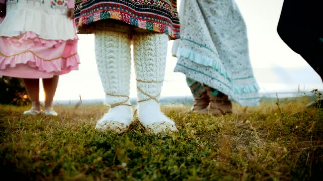 a person in bast shoes dancing on the green field. - славянская культура стоковые видео и кадры b-roll