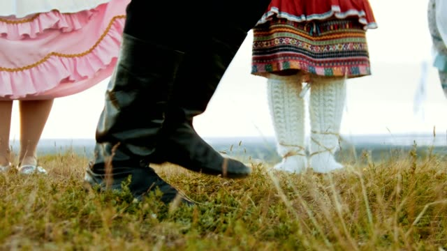 a person in black leather boots dancing on the green field - dancing in ensemble. - славянская культура стоковые видео и кадры b-roll
