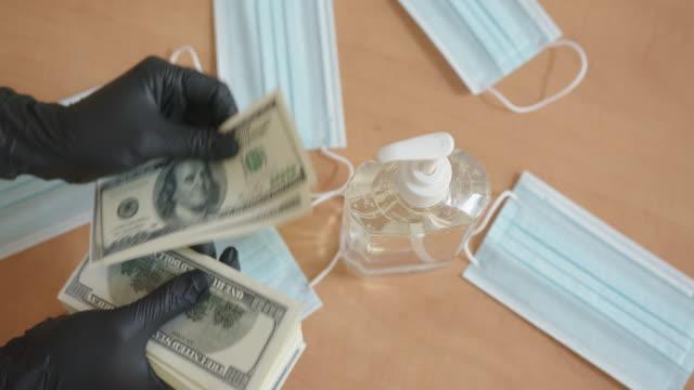 vídeos y material grabado en eventos de stock de la persona con guantes de protección negros cuenta billetes de dólar. protección durante el brote de virus de la gripe y la epidemia de coronavirus infeccioso. concepto de dinero de virus - accesorio financiero