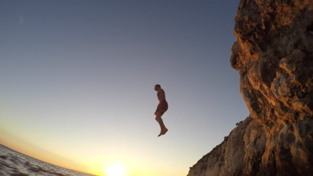 pov a person in the water watching a friend jump off a cliff at sunset - tuffarsi video stock e b–roll