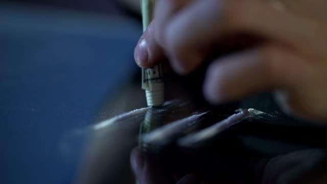 person einatmen kokain linie durch gerollten geldschein, sucht drogenproblem - suchtkranker stock-videos und b-roll-filmmaterial