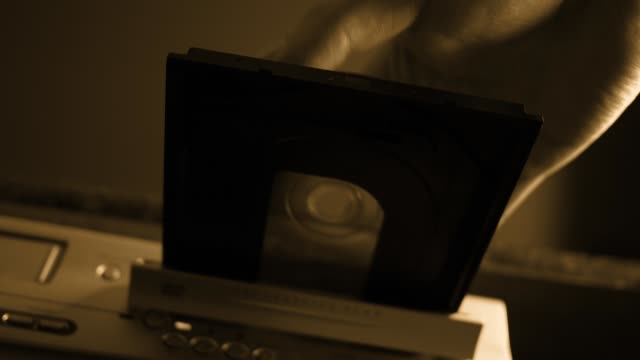 person inserts a dvd laser disc into the dvd player and pushes it into the tray - sepia verison - joseph kelly stock videos and b-roll footage