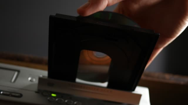 person inserts a dvd laser disc into the dvd player and pushes it into the tray - low angle - joseph kelly stock videos and b-roll footage