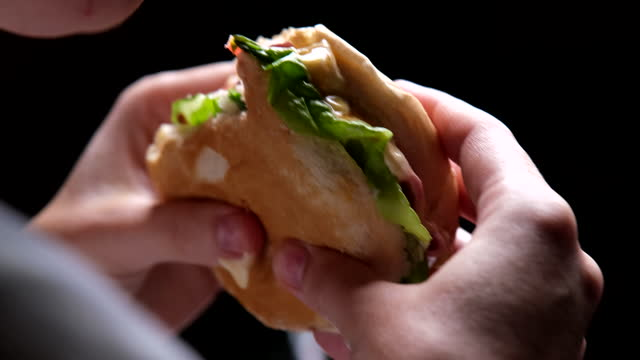 Person is eating sandwich, hands and face are getting dirty. Close-up video