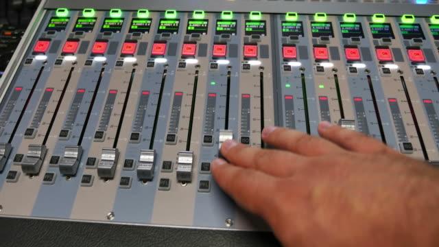 en person drar upp rattarna en ljudmixer i en studio - intoning bildbanksvideor och videomaterial från bakom kulisserna