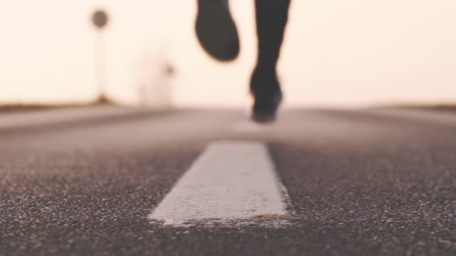 SLO MO Person jogging on the road to nowhere Slow motion close-up low angle shot of an unrecognizable person stepping directly in front of a camera as jogging toward on a road to nowhere. Also available in 4K resolution. human foot stock videos & royalty-free footage