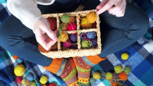 Person knitting with colorful balls of wool