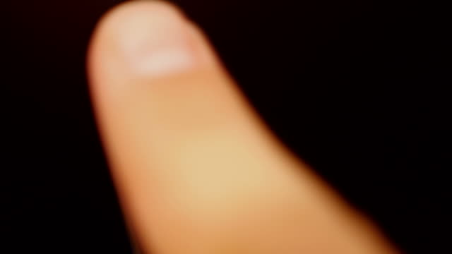 A person leaves a fingerprint on a dark flat surface