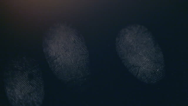 A person leaves his fingerprints on a dark surface