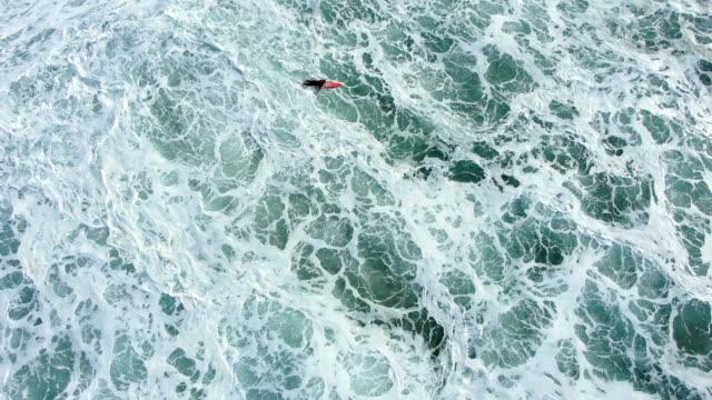 person lies on surfboard among ocean wave foam bird eye view - vídeo