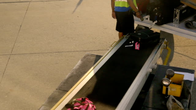 Person loading baggage onto plane video