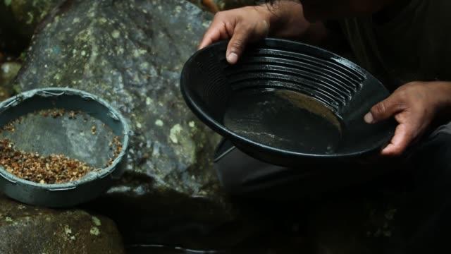 작은 개울에서 작은 금팬으로 금을 찾는 사람 - 패닝 스톡 비디오 및 b-롤 화면