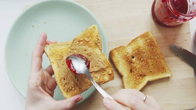 stockvideo's en b-roll-footage met persoon maak een sandwich met pindakaas en frambozen jam - geroosterd brood