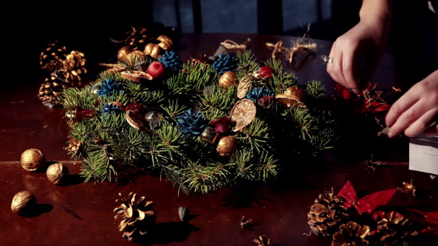 Person making a traditional Christmas wreath video