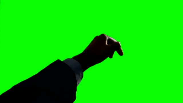 Person making hand gesture against green screen background