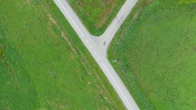 Person on a longboard on path through green grasslands Girl travelling on a longboard on an asphalted path with a forked road through green fields. fork stock videos & royalty-free footage