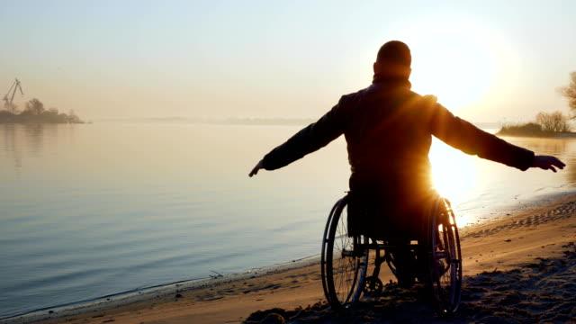 vídeos y material grabado en eventos de stock de persona en silla de ruedas, manos arriba, puesta del sol, solo desactivado en - deportes en silla de ruedas