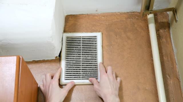 vídeos de stock e filmes b-roll de person opens a dusty ventilation grill. - sem higiene