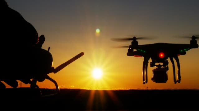 Person operating drone quadcopter aircraft via remote control at sunset video