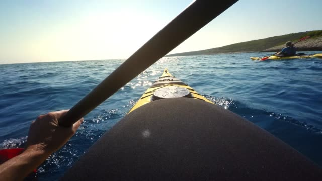 vídeos de stock, filmes e b-roll de pessoa do pov que rema um caiaque do mar na luz do sol - remo esporte aquático