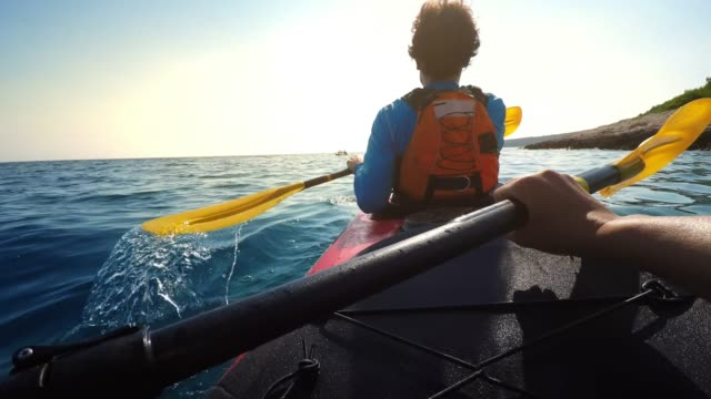 POV Person paddling in a tandem sea kayak on a sunny day
