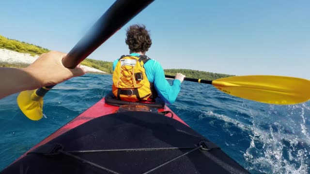POV Person paddling in the back of a tandem sea kayak in sunshine