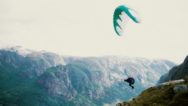 person paragliding in mountains in norway - парапланеризм стоковые видео и кадры b-roll