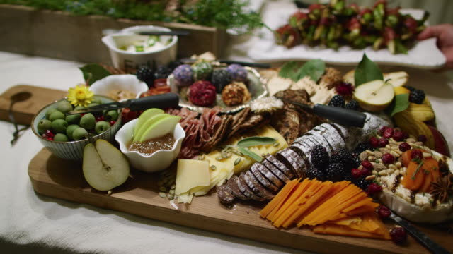 a person places an appetizer in the background while the camera pans an appetizer charcuterie meat/cheeseboard with various fruit, sauces, and garnishes on a table at an indoor celebration/party - cucina francese video stock e b–roll