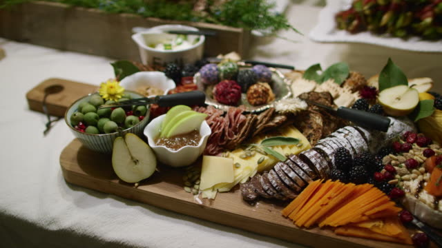 A Person Places an Appetizer in the Background While the Camera Pans an Appetizer Charcuterie Meat/Cheeseboard with Various Fruit, Sauces, and Garnishes on a Table at an Indoor Celebration/Party