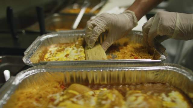 vídeos de stock, filmes e b-roll de uma pessoa coloca tamales acondicionados em uma assadeira com queijo e arroz em uma cozinha comercial num restaurante mexicano de metal - luvas