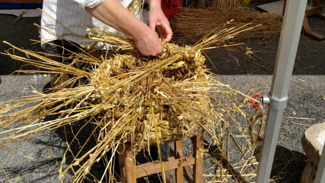 A person platting the top of a hand made straw basket