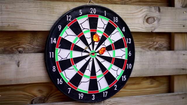 Person playing darts outdoors, enjoying hobby, fun activity. Entertaining game video