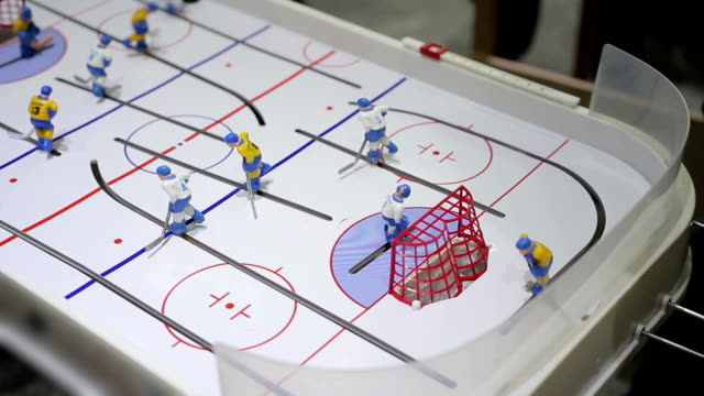 Person playing table ice hockey, hitting puck into opposing net, indoor activity video