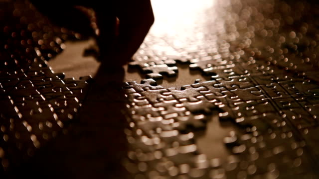 person positions last pieces of puzzle into the picture - puzzle video stock e b–roll