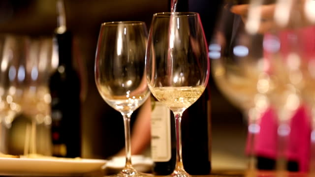 Person pouring and shaking white wine in glass, tasting of exclusive varieties Person pouring and shaking white wine in glass, tasting of exclusive varieties winetasting stock videos & royalty-free footage