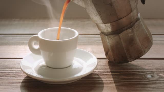 人は、小さなカップにコーヒーを注ぐ - コーヒー点の映像素材/bロール