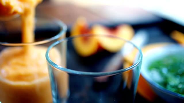 Personne verse le smoothie orange en verre - Vidéo