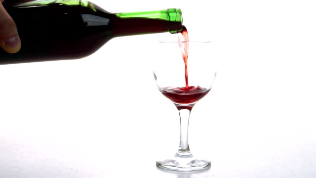 Person pours red wine into glass in room of appartment video