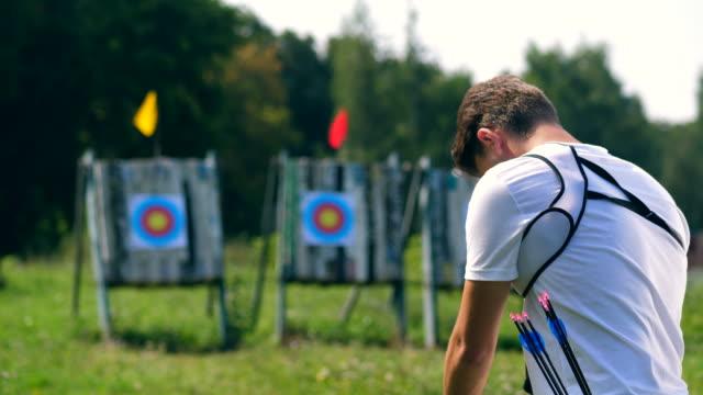 vidéos et rushes de une personne prépare un arc pour tirer la cible. - tir à l'arc