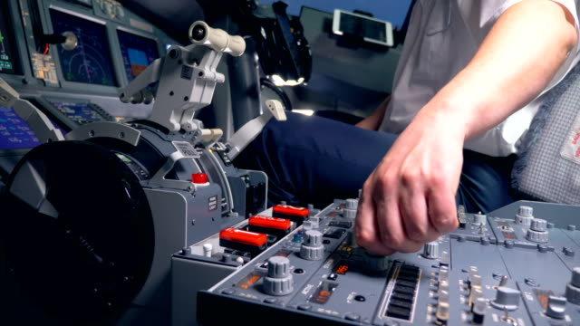 Person pushes buttons on a plane dashboard, close up.