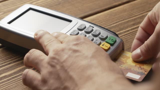 pos ターミナル ボタンとスワイプ クレジット カードの支払いを押す人 - グリーティングカード点の映像素材/bロール