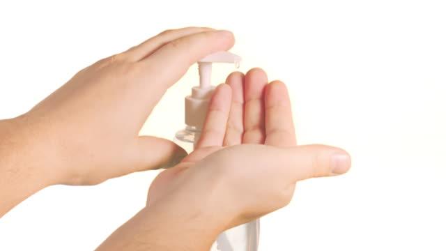 vídeos y material grabado en eventos de stock de una persona poniendo desinfectante de manos sobre un fondo blanco - hand sanitizer